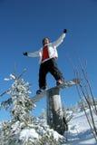 snowboarder standing on tree stump Royalty Free Stock Photo