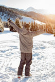 Snowboarder stands mountain top with his arms raised Stock Photos