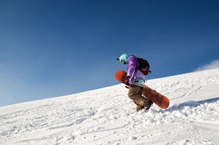Snowboarder stands and walks on mountain slopes of an extinct volcano Elbrus Royalty Free Stock Photography