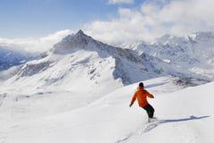 Snowboarder su una priorità bassa della montagna Fotografie Stock Libere da Diritti