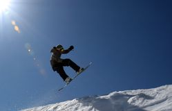 Snowboarder and Sun. Snowboarder jumps with the sun behind him Stock Image