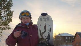 Snowboarder superior da mulher com o snowboard que descansa no recurso do inverno na montanha filme