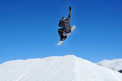 Snowboarder takeing off from a jump ramp Royalty Free Stock Photo