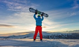 Snowboarder on the top of mountain, Alpine scenery. Snowboarder on the top of mountain, ready to downhill run off piste. European Alpine scenery in sunset light Stock Photography
