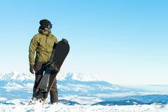 Snowboarder at the top of a mountain. Enjoying the view Stock Images