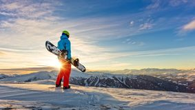 Snowboarder on the top of mountain, Alpine scenery. Snowboarder on the top of mountain, ready to downhill run off piste. European Alpine scenery in sunset light Royalty Free Stock Image