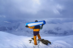 Snowboarder is turned back over  cliff snowy weather in  mountains. Stock Photos