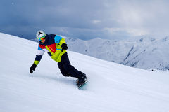 Snowboarder turns on   slope against the dark sky with clouds Royalty Free Stock Image