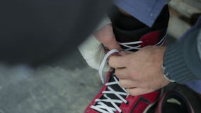 Snowboarder tying shoelaces. Close-up stock video footage