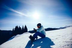 Snowboarder use smatphone na zimy góry wierzchołku Obrazy Royalty Free