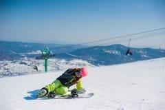 Snowboarder in vestiti gialli che riposano sulla montagna Fotografia Stock