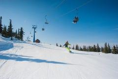 Snowboarder in vestiti gialli che riposano sulla montagna Fotografia Stock Libera da Diritti