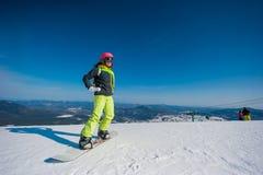 Snowboarder in vestiti gialli che riposano sulla montagna Fotografie Stock