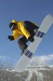 Snowboarder W doskakiwaniu Podczas gdy Pokazywać zwycięstwo znaka Przeciw niebu Zdjęcie Royalty Free