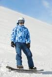 Snowboarder w narciarskiego kostiumu stojakach na snowboard zdjęcia royalty free