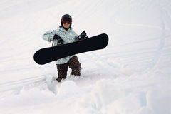 Snowboarder walking in deep show. Snowboarder walking through deep powder snow Royalty Free Stock Photos