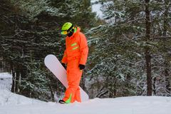 Snowboarder walking through the forest. Snowboarder dressed in orange suit walking through the forest royalty free stock images