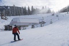 Snowboarder beside Whistler village gondola base stock image