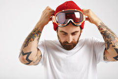 Snowboarder in white t-shirt putting on goggles stock photography