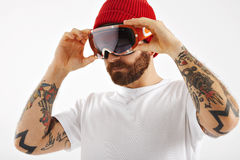 Snowboarder in white t-shirt putting on goggles. Young man puttin on black snowboard glasses wearing a red beanie and a white blank t-shirt on white background Stock Photos