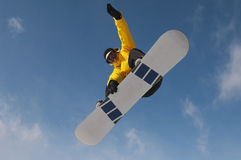 Snowboarder In Winter Clothes Jumping Against Sky. Low angle view of male snowboarder in winter clothes jumping against sky Royalty Free Stock Images