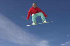Snowboarder In Winter Clothes Jumping Against Sky. Low angle view of young male snowboarder in winter clothes jumping against sky Stock Photography
