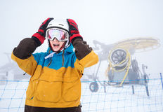 Snowboarder woman in mountains. Emotional portrait of woman snowboarder on background of falling snow and snow gun in the snowy weather in the high mountains of Royalty Free Stock Image