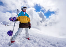 Snowboarder woman in mountains. Portrait of woman snowboarder on background beautiful landscape of snowy high mountains of Caucasus at Krasnaya Polyana, standing Royalty Free Stock Photos