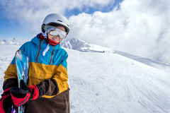 Snowboarder woman in mountains. Portrait of woman snowboarder on background beautiful landscape of snowy high mountains of Caucasus at Krasnaya Polyana, standing Royalty Free Stock Images
