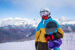Snowboarder woman in mountains. Portrait of woman snowboarder on background beautiful landscape of snowy high mountains of Caucasus at Krasnaya Polyana, standing Stock Images