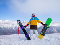 Snowboarder woman in mountains. Portrait of woman snowboarder on background beautiful landscape of snowy high mountains of Caucasus at Krasnaya Polyana, standing Stock Photo