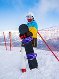 Snowboarder woman in mountains. Portrait of woman snowboarder on background beautiful landscape of snowy high mountains of Caucasus at Krasnaya Polyana, standing Royalty Free Stock Image