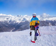 Snowboarder woman in mountains. Portrait of woman snowboarder on background beautiful landscape of snowy high mountains of Caucasus at Krasnaya Polyana, standing Royalty Free Stock Photo