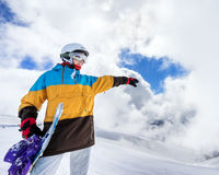 Snowboarder woman in mountains. Portrait of woman snowboarder pointing way on background beautiful landscape of snowy high mountains of Caucasus at Krasnaya Stock Image