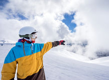 Snowboarder woman in mountains. Portrait of woman snowboarder pointing way on background beautiful landscape of snowy high mountains of Caucasus at Krasnaya Royalty Free Stock Image