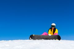 Snowboarder woman sitting on snow mountain slope Stock Photography