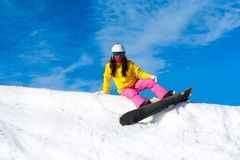 Snowboarder woman sitting on snow mountain slope Stock Image