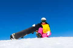Snowboarder woman sitting on snow mountain slope Royalty Free Stock Photography