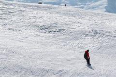 Snowboarder y esquiador cuesta abajo en cuesta fuera de pista de la nieve Fotos de archivo