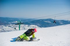 Snowboarder in yellow clothes resting on the mountain Stock Photo