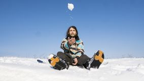 Snowboarder z długie włosy obsiadaniem na snowboard i rzuca snowball w powietrzu Krańcowy zima sport zdjęcia stock