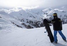 Snowboarderanseende med hans snowboard på lutning Royaltyfri Bild