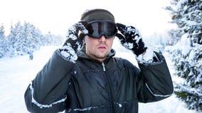 Snowboarderanseende på en skidalutning i vinter och uppehällen hans händer en skidamaskering Arkivfoton