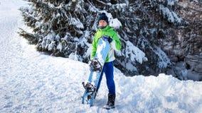 Snowboarderanseende på snön och uppehällena brädet Royaltyfri Fotografi