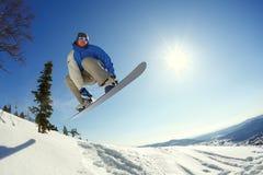 Snowboarderbanhoppning från språngbrädan mot himlen Royaltyfria Foton