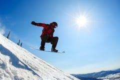 Snowboarderbanhoppning från språngbrädan mot himlen Royaltyfri Bild
