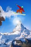 Snowboarderbanhoppning mot det Matterhorn maximumet i Schweiz Arkivfoton