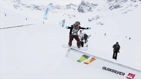 Snowboarderdia op ijzersleep op helling cameraman Landschap van sneeuwbergen competition stock footage