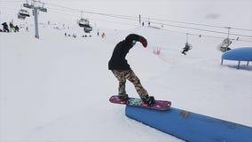 Snowboarderdia op springplank bij skitoevlucht in bergen Extreme tik cameraman Mensen stock footage