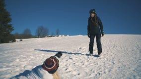 Snowboarderen eller skidåkaren och fotografen gör fotoperiod på att skida det mitt- skottet för semesterorten arkivfilmer